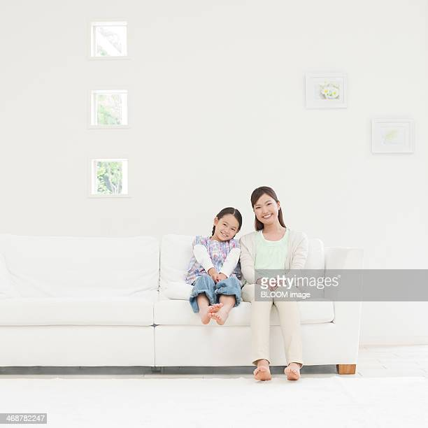 Mother And Daughter Sitting On Couch