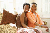 Mother and daughter sitting on couch, smiling