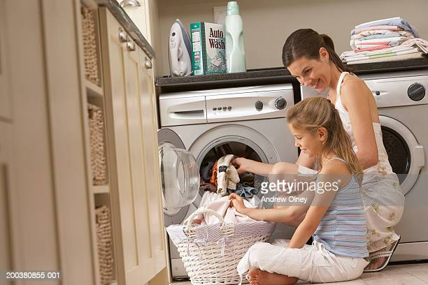 Mother and daughter (7-9) sitting on floor sorting through laundry