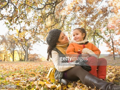 Mother and daughter sitting on grass and leaves : Stock Photo