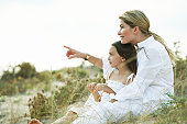 Mother and daughter (6-8) sitting on grassy dunes, mother pointing