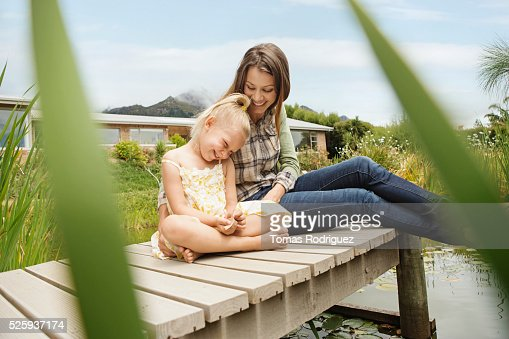 Mother and daughter (4-5) sitting on jetty : Stock Photo