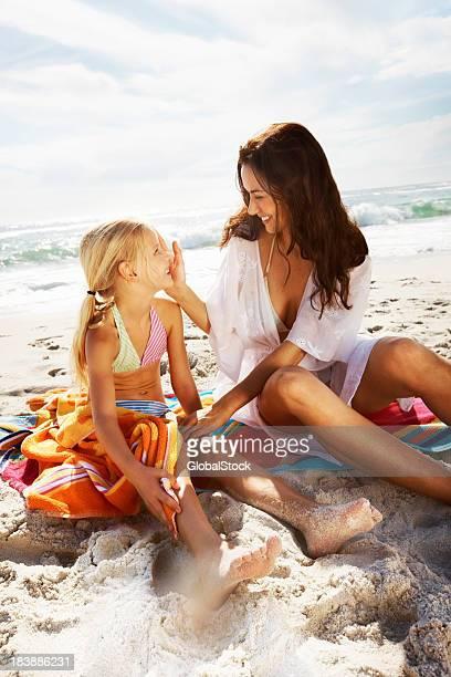 Mutter und Tochter sitzen auf dem sand am Strand