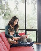Mutter und Tochter (2-4) sitzt auf sofa lesen Buch