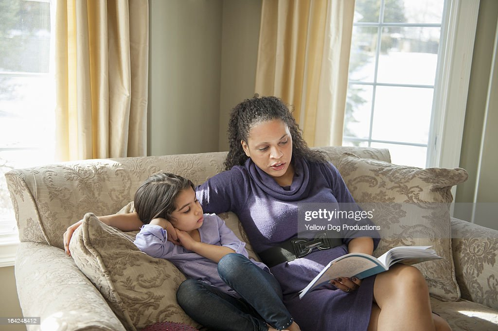 Mother and daughter (6) sitting on sofa, reading : Stock Photo