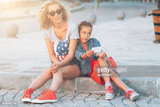 Mother and daughter sitting on street and waiting