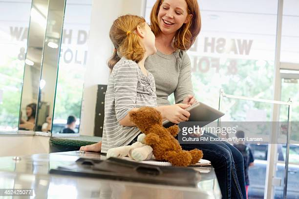 Mother and daughter sitting on washing machine using digital tablet