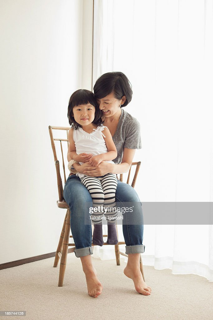 Mother and daughter sitting on wooden chair,  portrait : Stock Photo