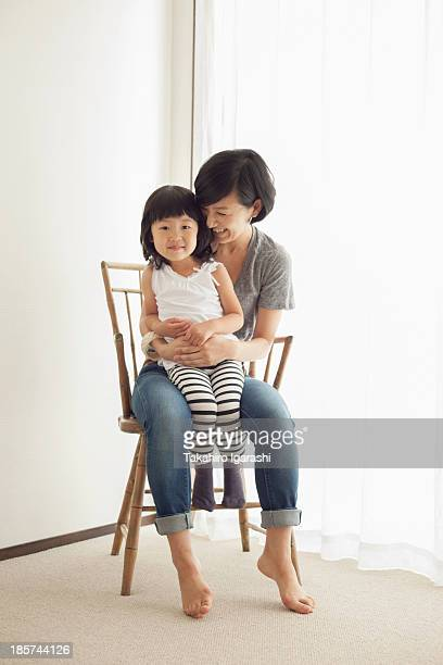 Mother and daughter sitting on wooden chair,  portrait