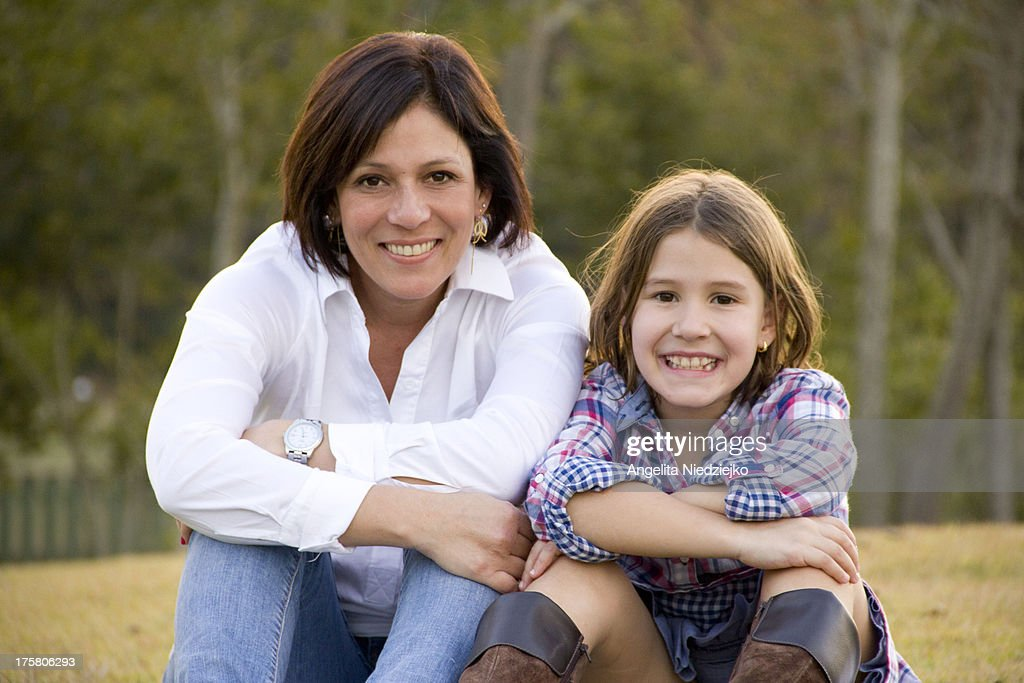Mother and daughter sitting side by side smiling : Stock Photo