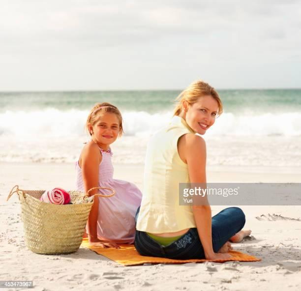 Mutter und Tochter sitzen zusammen am Strand, Picknick