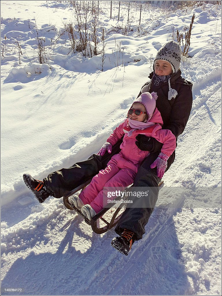Mother and daughter sledging : Stock Photo