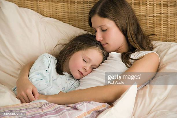 Mother and daughter (4-5) sleeping in bed, elevated view