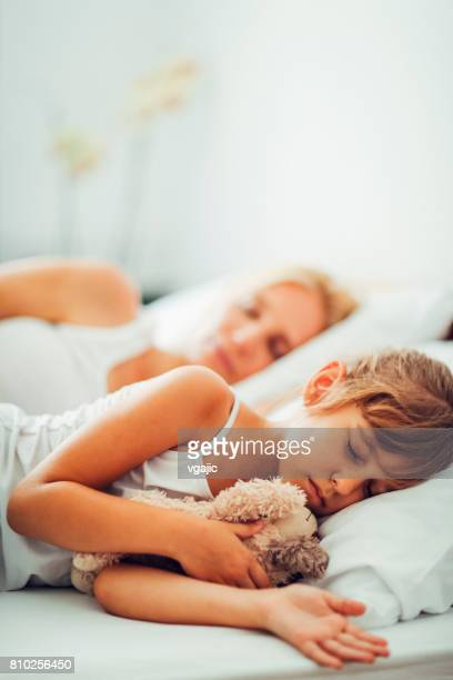Mother and Daughter sleeping in their bed