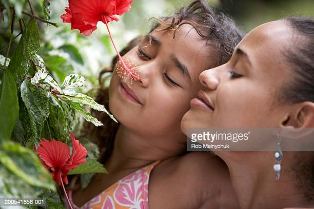Mother and daughter (5-7) smelling flower, smiling