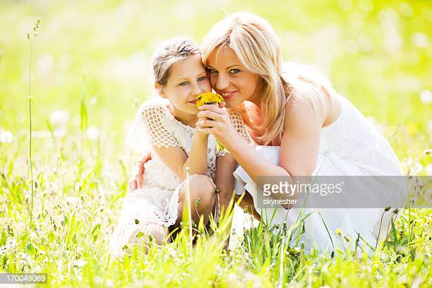 Mutter und Tochter riechen Blumen in der Natur.