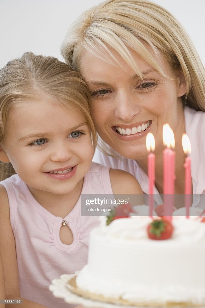Mother and daughter smiling at birthday cake : Stock Photo