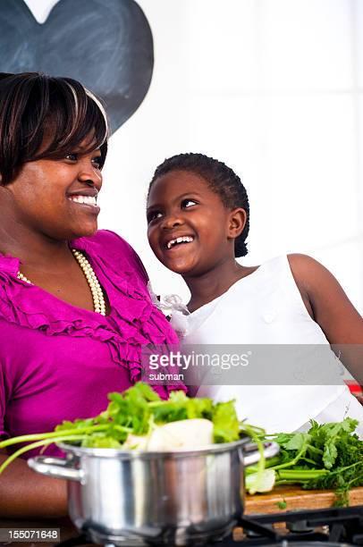 Mãe e filha, sorrindo para os outros na cozinha