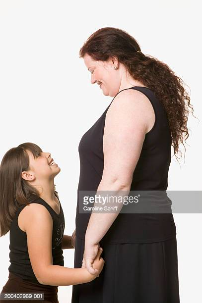 Mother and daughter (8-10) smiling at one another, side view