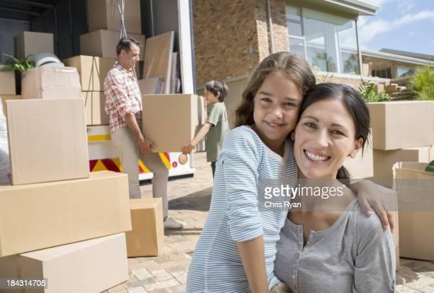 Mãe e filha a sorrir por Camião de Mudanças na Entrada para Automóvel