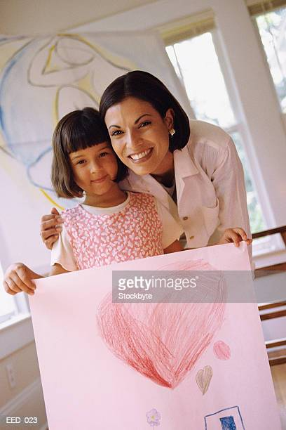 Mother and daughter smiling; daughter holding picture of heart