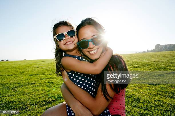 Mother and daughter smiling in field