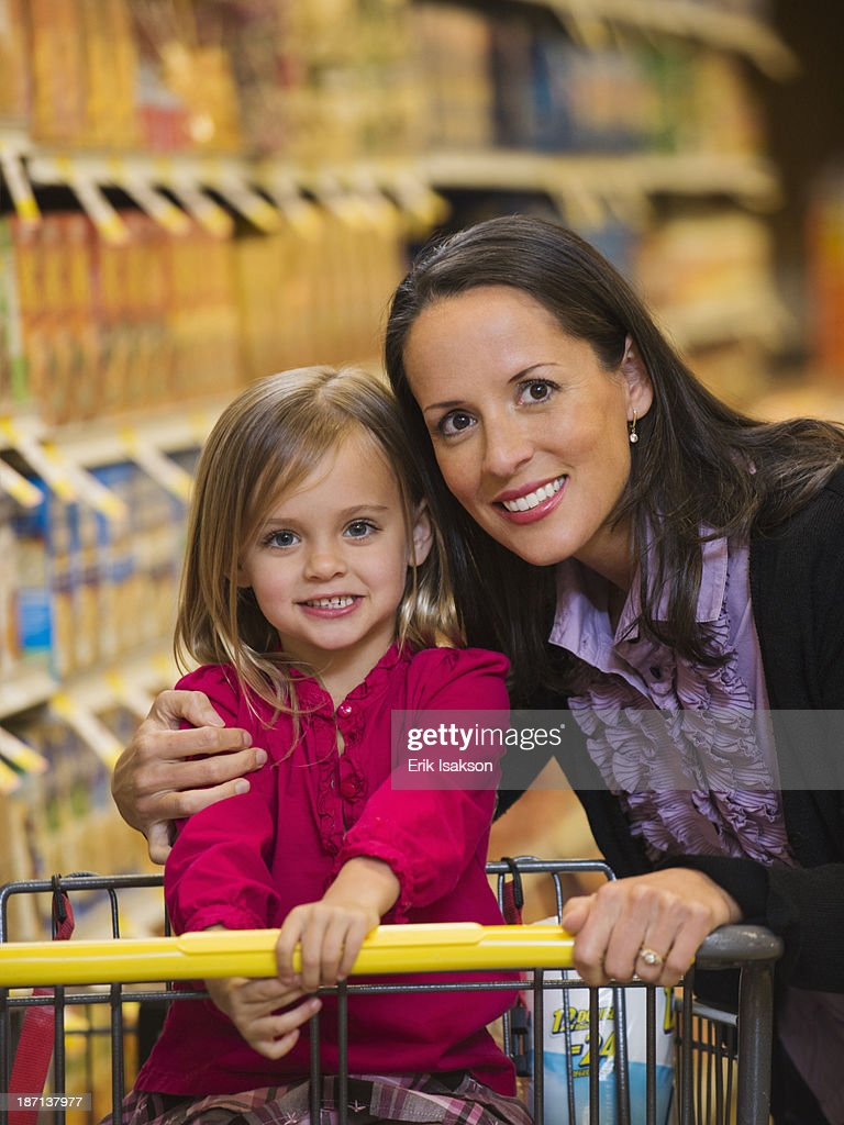 Mother and daughter smiling in grocery store : Stock Photo