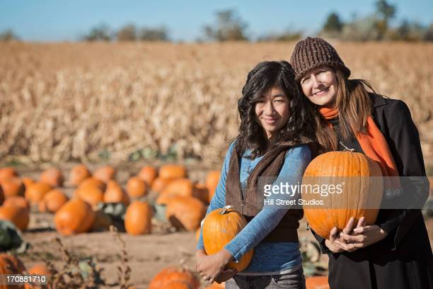 Mother and daughter smiling in pumpkin patch