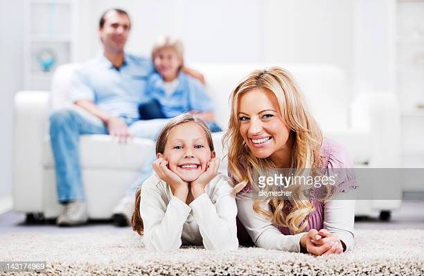 Mother and daughter smiling, looking at the camera.
