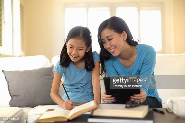 Mother and daughter smiling on sofa