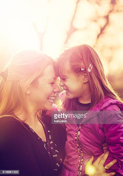 Mother and daughter smiling together at sunset