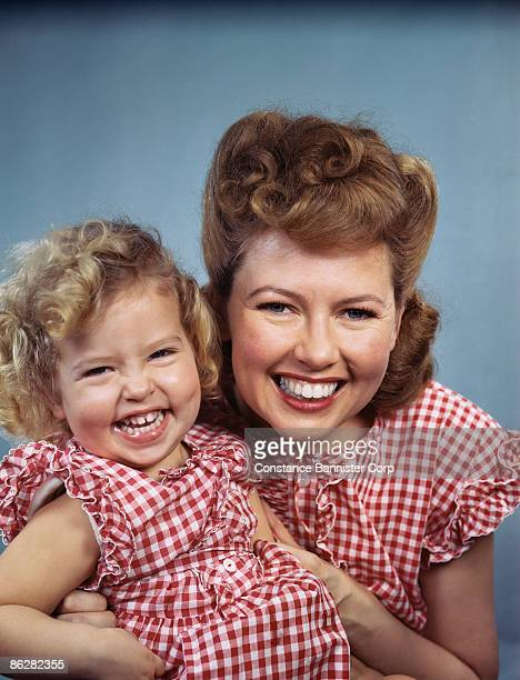 Mother and daughter smiling wearing red checkered outfits