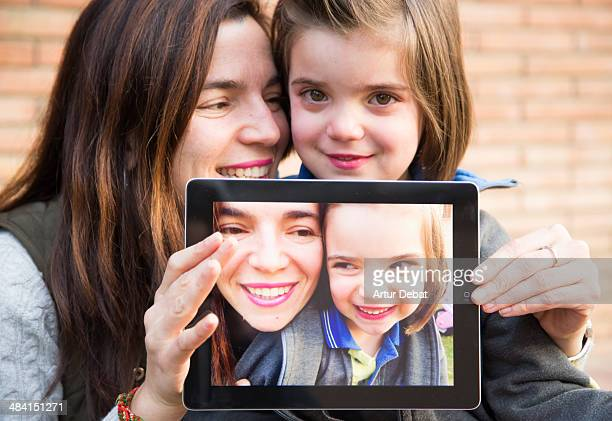 Mother and daughter smiling with his photo on the screen of an IPad tablet