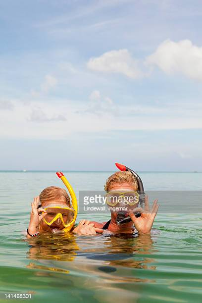 Mother and daughter snorkeling in sea