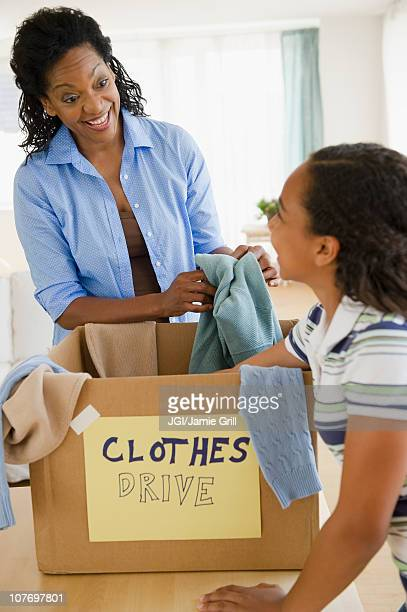 Mother and daughter sorting clothes for clothes drive