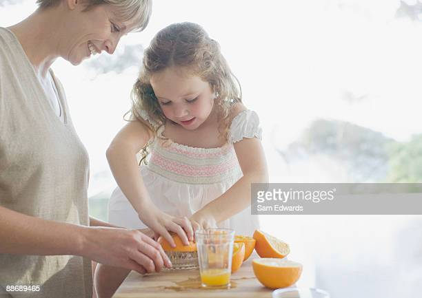 Mother and daughter squeezing oranges