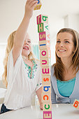 Mother and daughter stacking blocks together