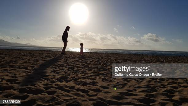 Mother And Daughter Standing At Beach Against Sky During Sunset