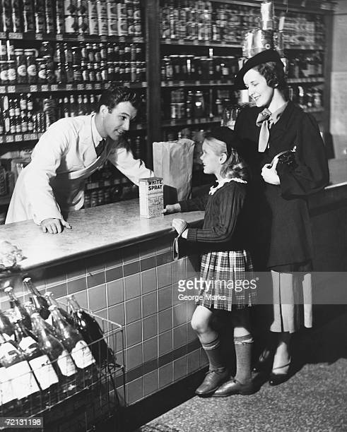 Mother and daughter (8-9) standing at counter, talking to shop assistant (B&W)