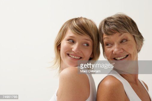 Mother and daughter standing back to back, smiling