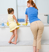 Mother and daughter standing by bathtub