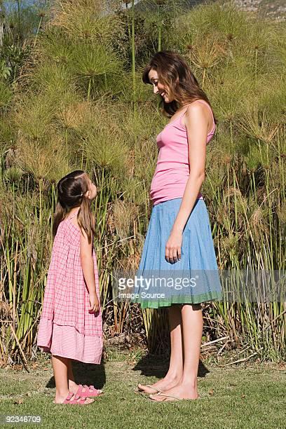 Mère et fille debout face à face et souriant
