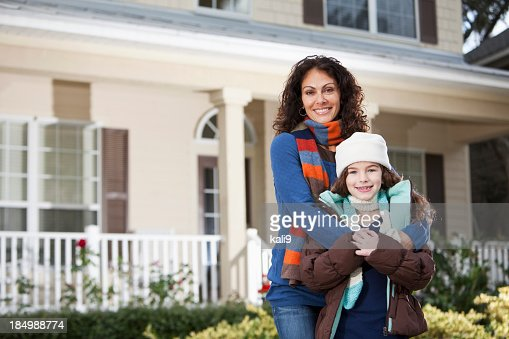 Mother and daughter standing in front of house