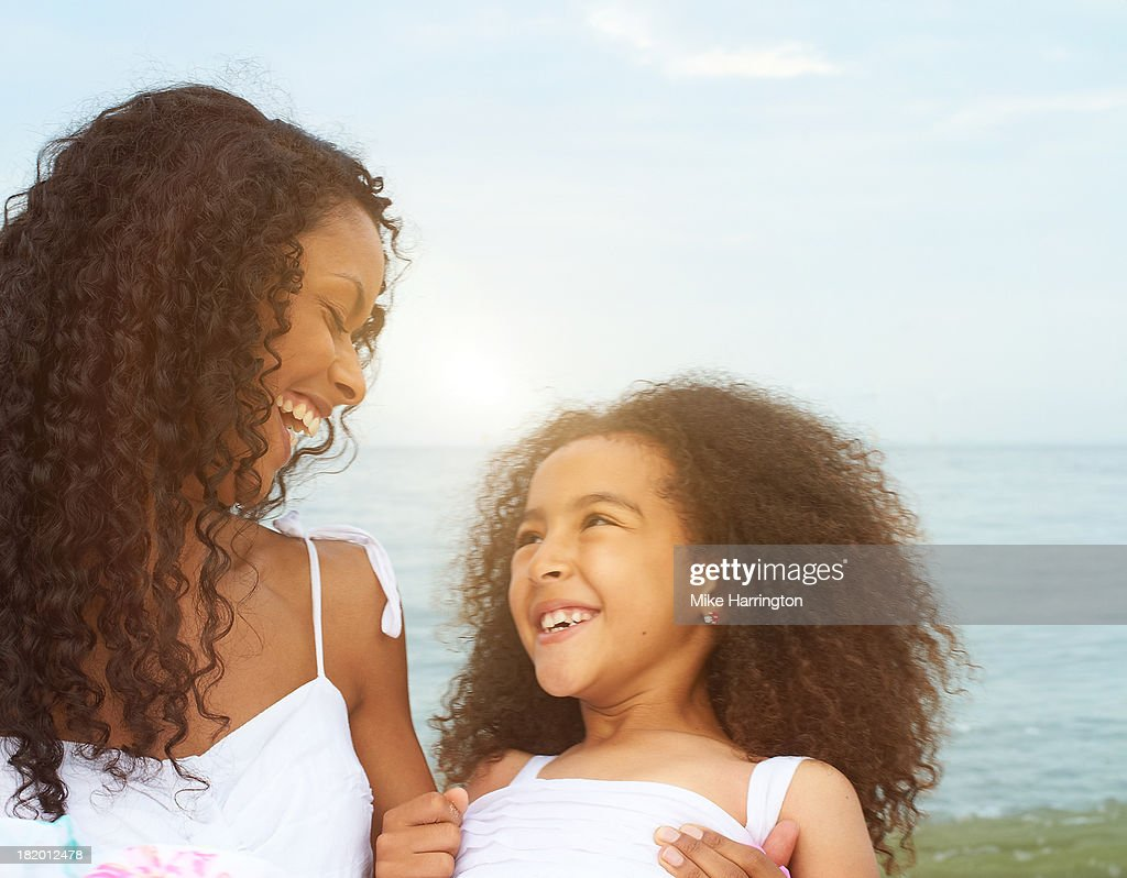 Mother and daughter standing on beach laughing : Stock Photo
