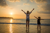 Mother and daughter standing on the sunset beach