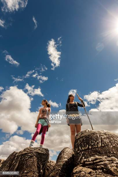 Mother and daughter standing on top of cliff
