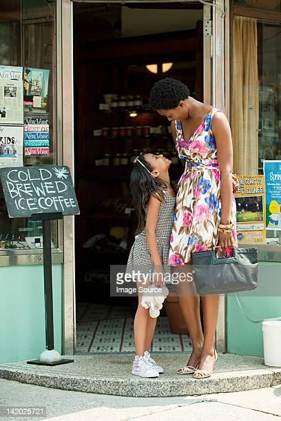 Mutter und Tochter stehen außerhalb coffee shop