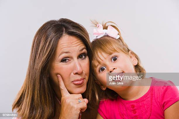 Mother and daughter sticking tongue out, portrait