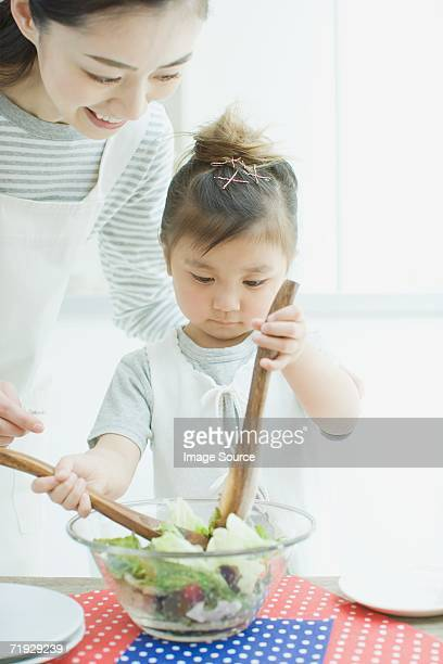 Mother and daughter stirring salad