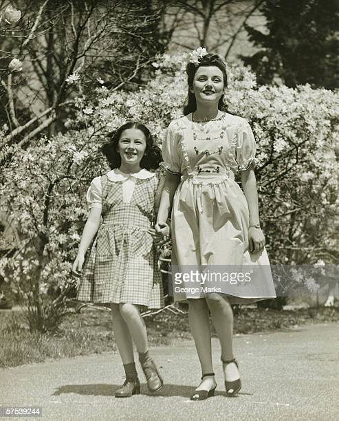 Mother and daughter (8-9) strolling in park, (B&W)